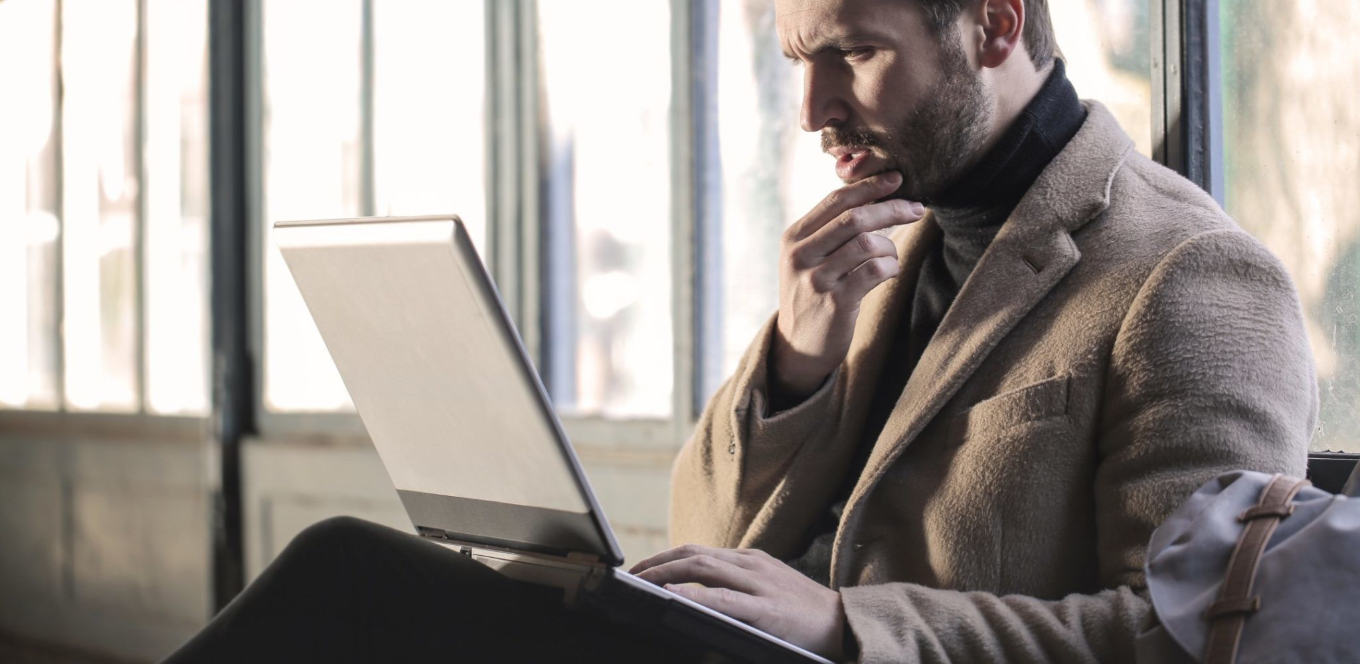 Een man kijkt naar het scherm van zijn laptop